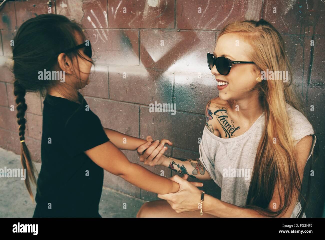 Glückliche Mutter und Tochter, die Hand in Hand gegen die Wand Stockbild