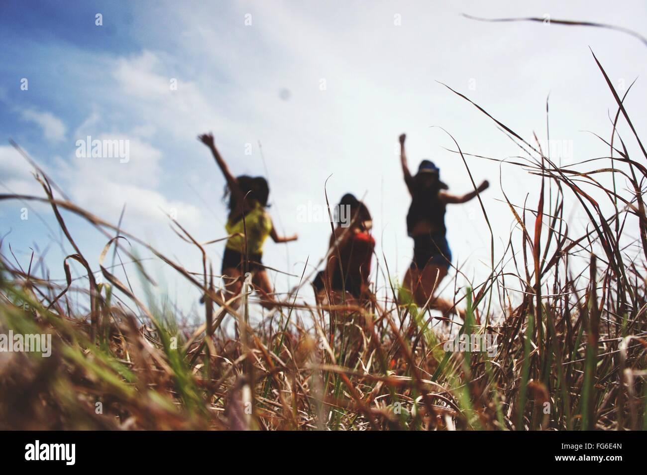 Frauen, die auf auffangene gegen bewölktem Himmel springen Stockbild