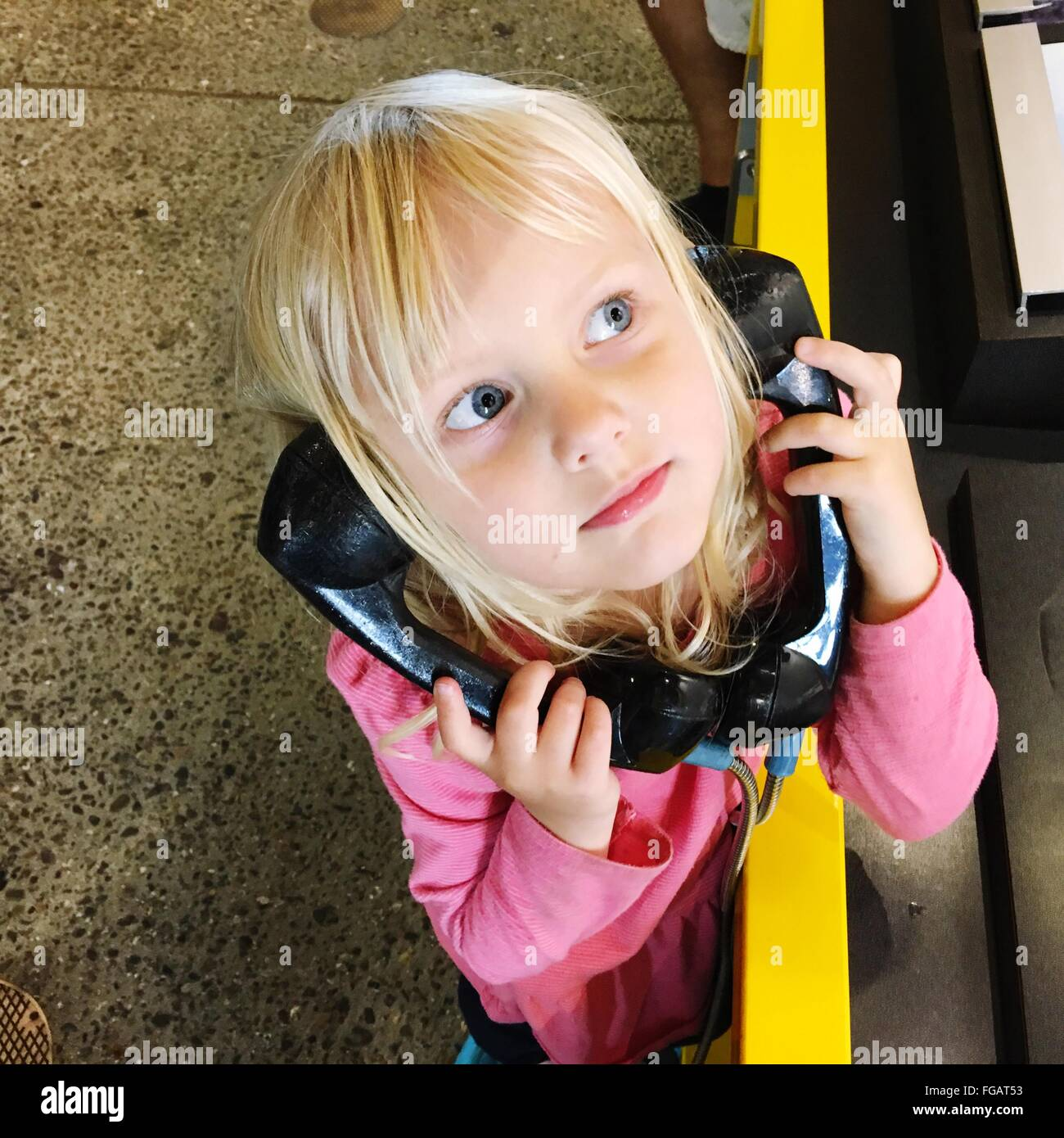 High Angle View Of Girl Telefon Empfänger auf Stand halten Stockbild