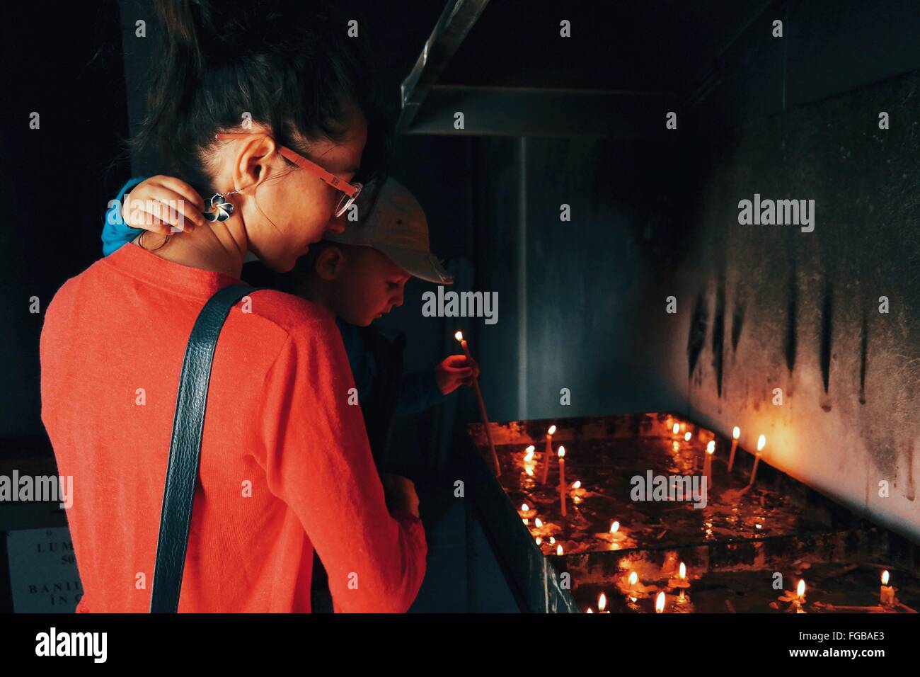 Sohn mit Kerze mit Mutter In der Kirche Stockbild