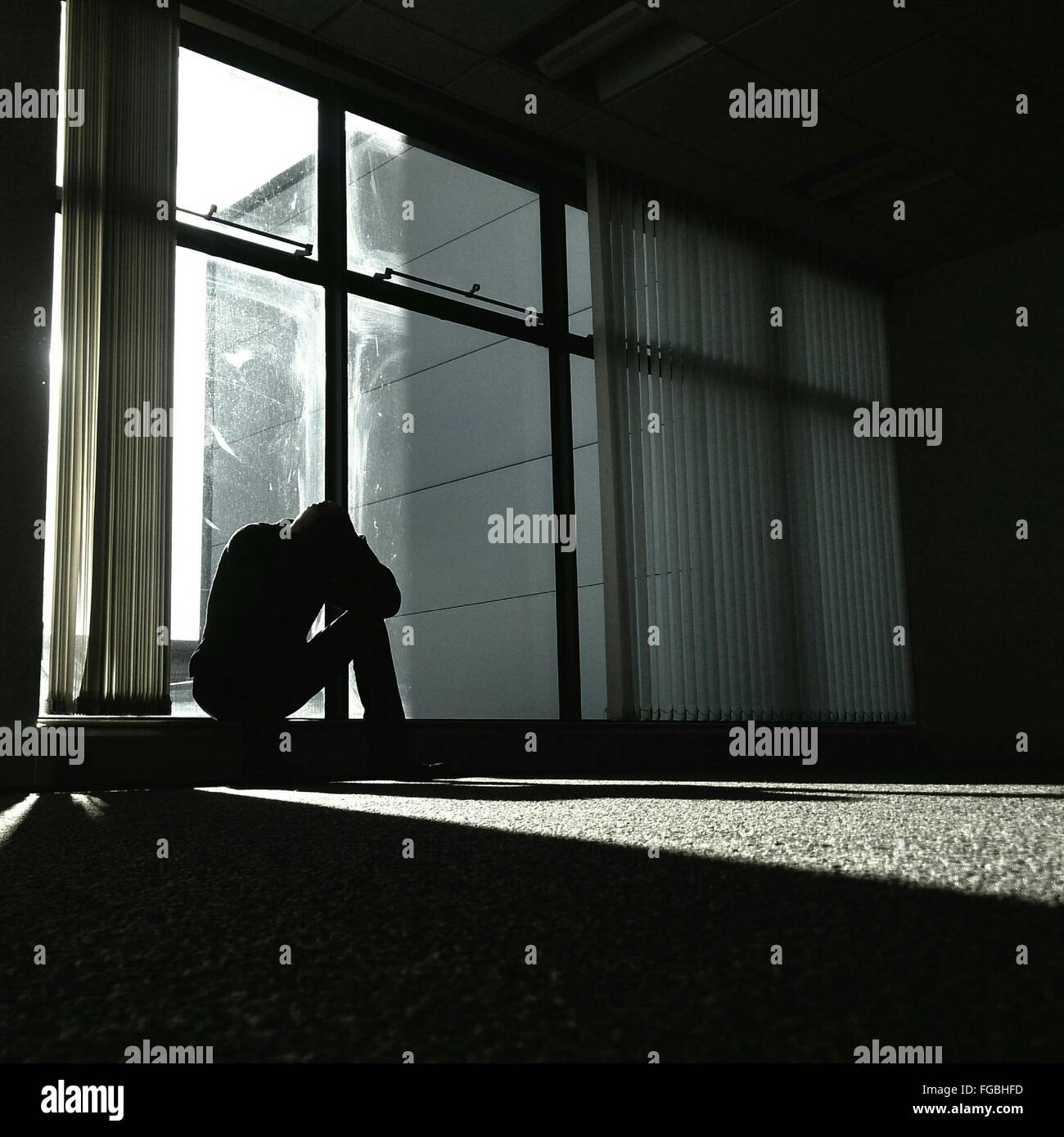 Depressive Menschen Glasfenster zu Hause sitzen Stockbild