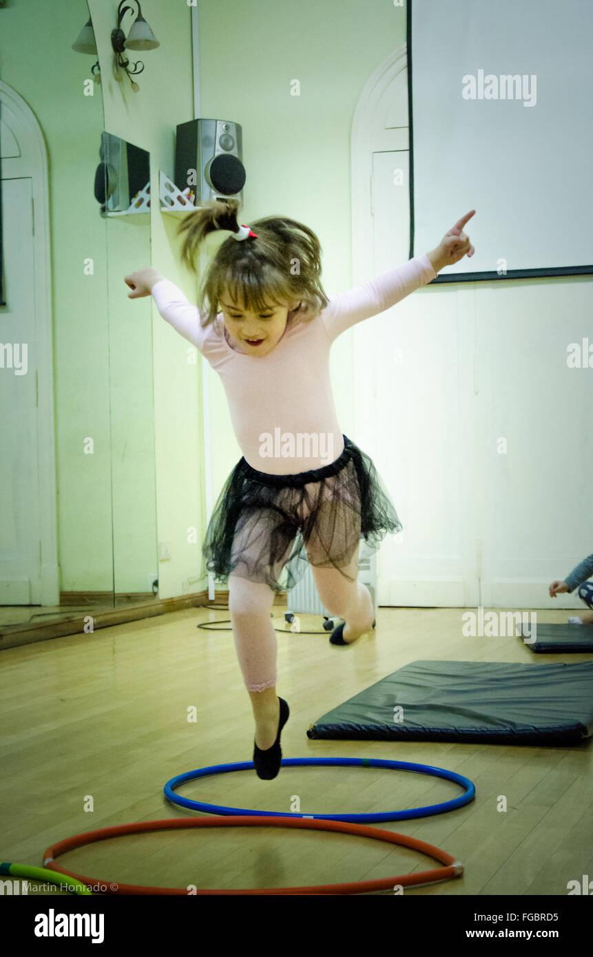 Vorderansicht des Mädchen springen über Reifen im Tanzstudio Stockbild