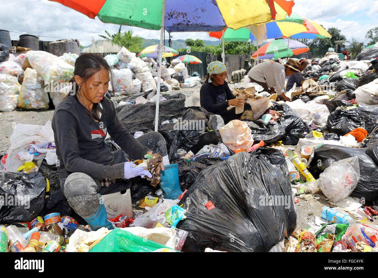 Frauen arbeiten Mülltrennung und Weiterverkauf in einem Junk-e-Shop in der Nähe der Quezon City integrierte Stockbild