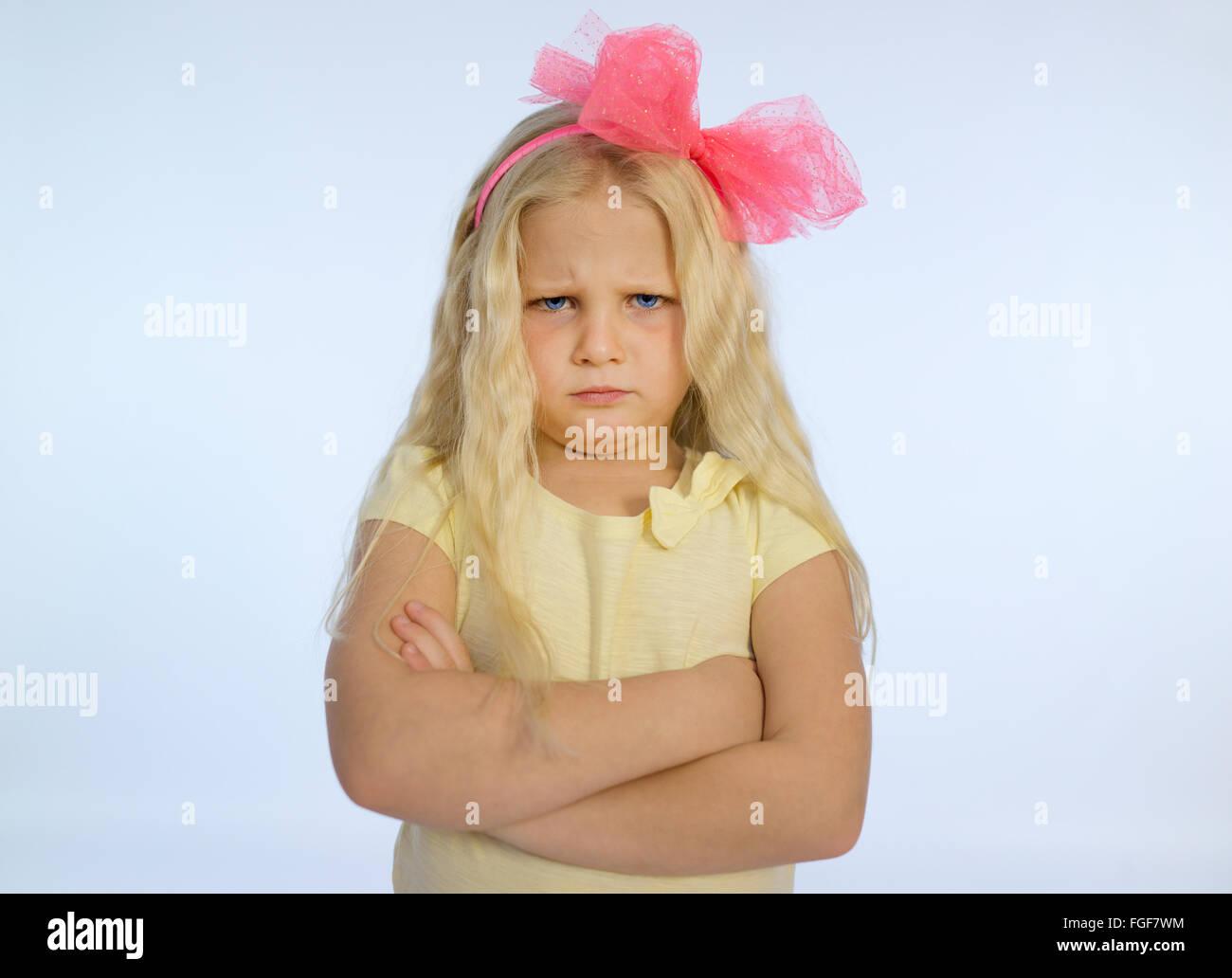 Junges Mädchen mit langen blonden Haaren und verschränkten Armen, runzelt die Stirn mit einem traurigen Stockbild