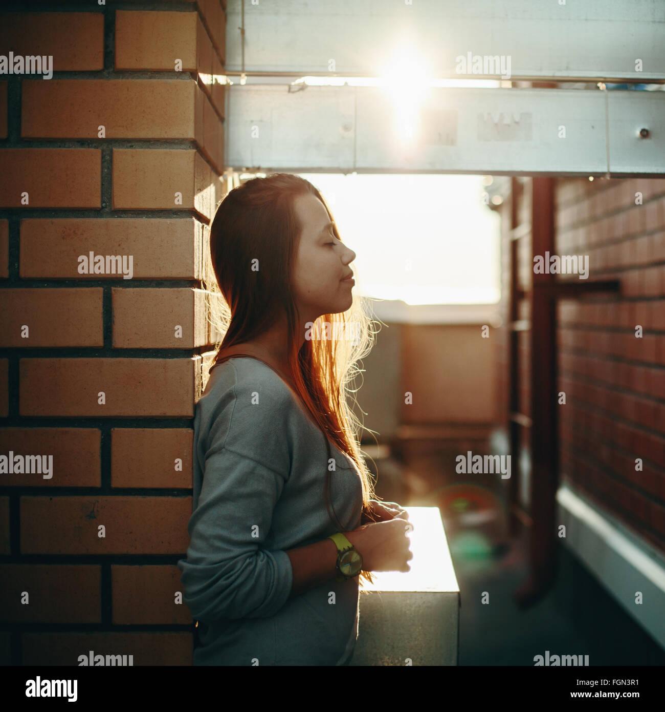 Junge Frau stehen auf einer Straße mit geschlossenen Augen im Sonnenuntergang Licht. Selektiven Fokus, Lens Stockbild