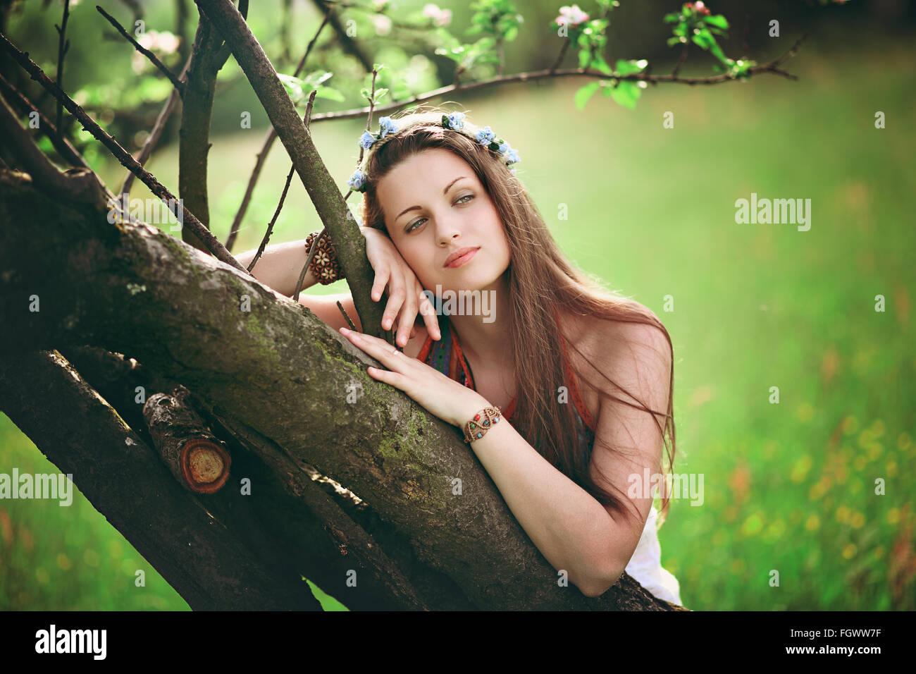 Böhmische Frau auf Frühling Baum gelehnt. Hippie und romantisch Stockbild