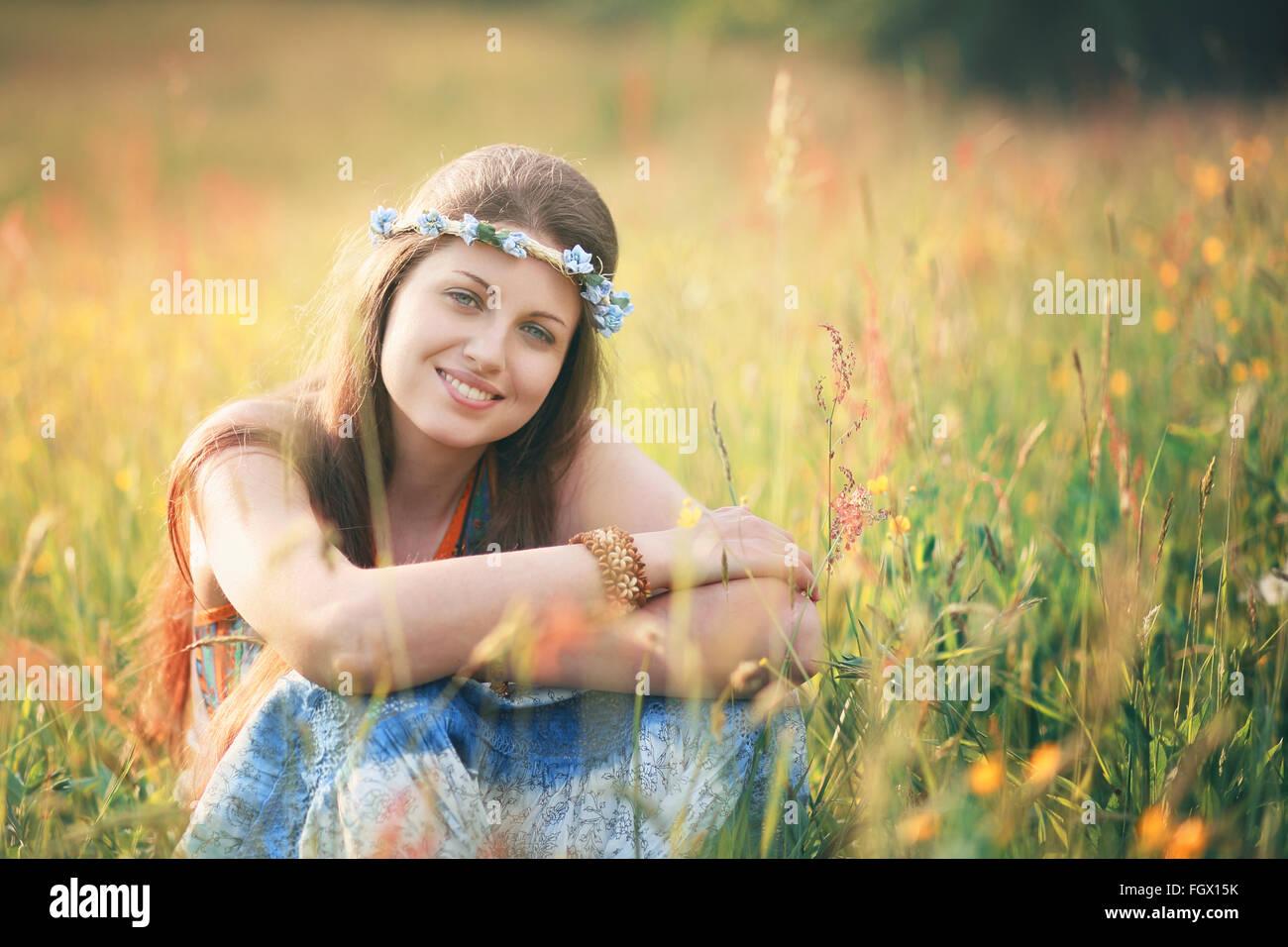 Lächelnde romantische Frau in Blumenwiese. Hippie und Zigeuner Kleid Stockbild