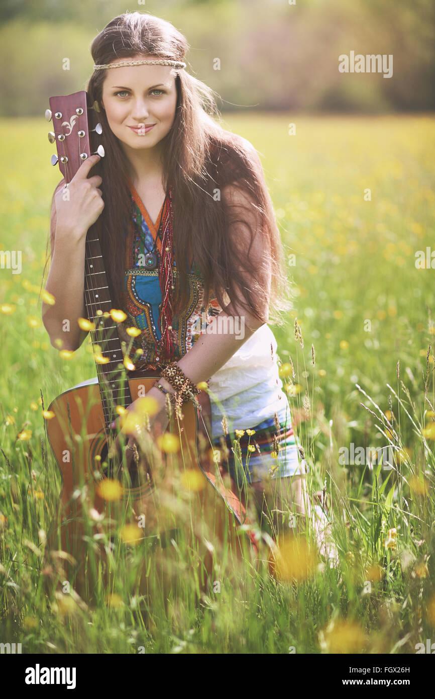 Wunderschöne Hippie-Frau posiert mit Gitarre. Natur-Harmonie Stockbild