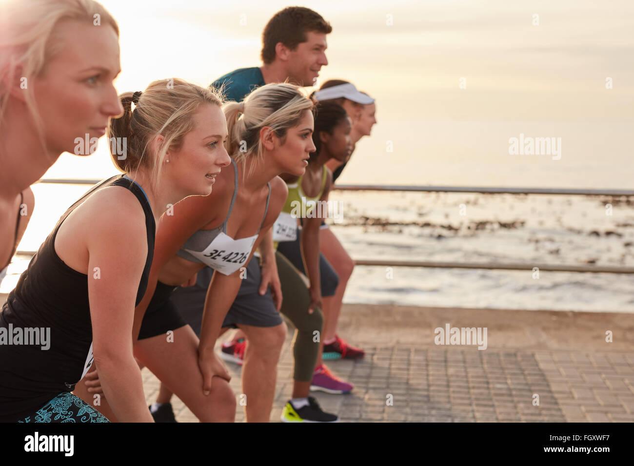 Läufer auf der Linie zu Beginn eines Rennens stehen. Gruppe von jungen Menschen eine Ausbildung für Marathon Stockbild