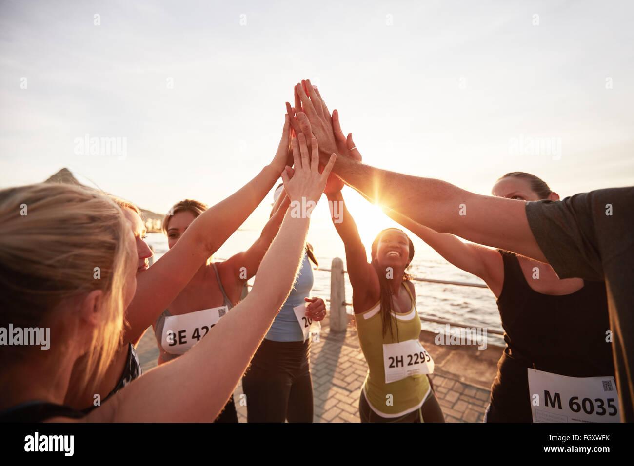Sportliche Team mit ihren Händen gestapelt zusammen Erfolge feiern. Marathonläufer geben hohe fünf. Stockbild
