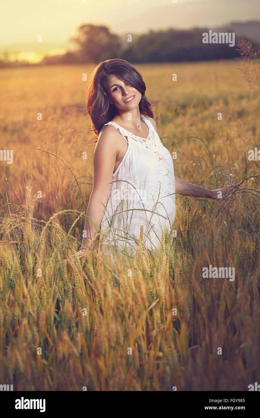 Schöne Frau posiert in einem Feld bei Sonnenuntergang. Sommer-Saison-Porträt Stockbild