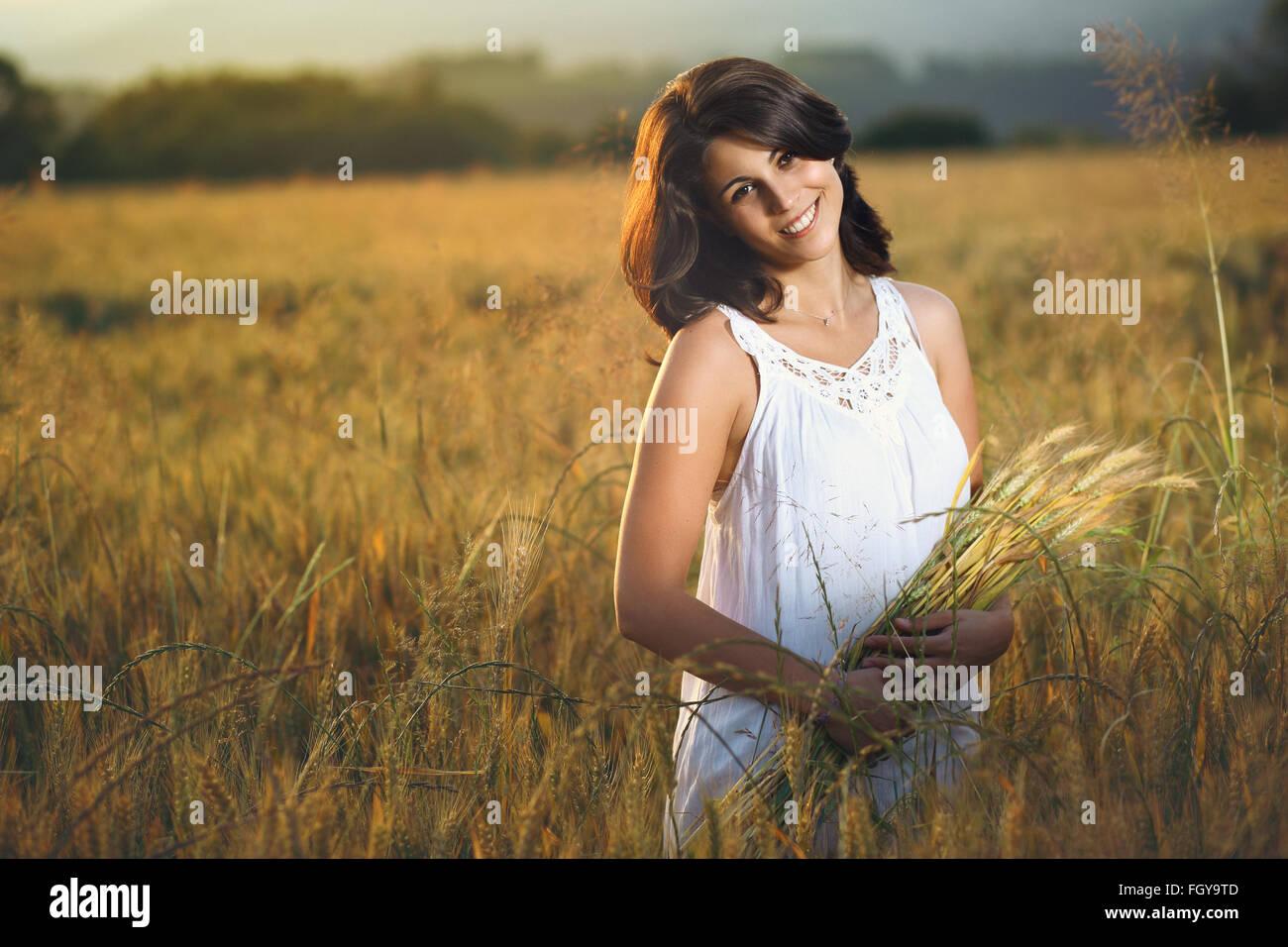 Wunderschöne lächelnde Frau in einem goldenen Feld bei Sonnenuntergang. Sommer-Saison-Porträt Stockbild