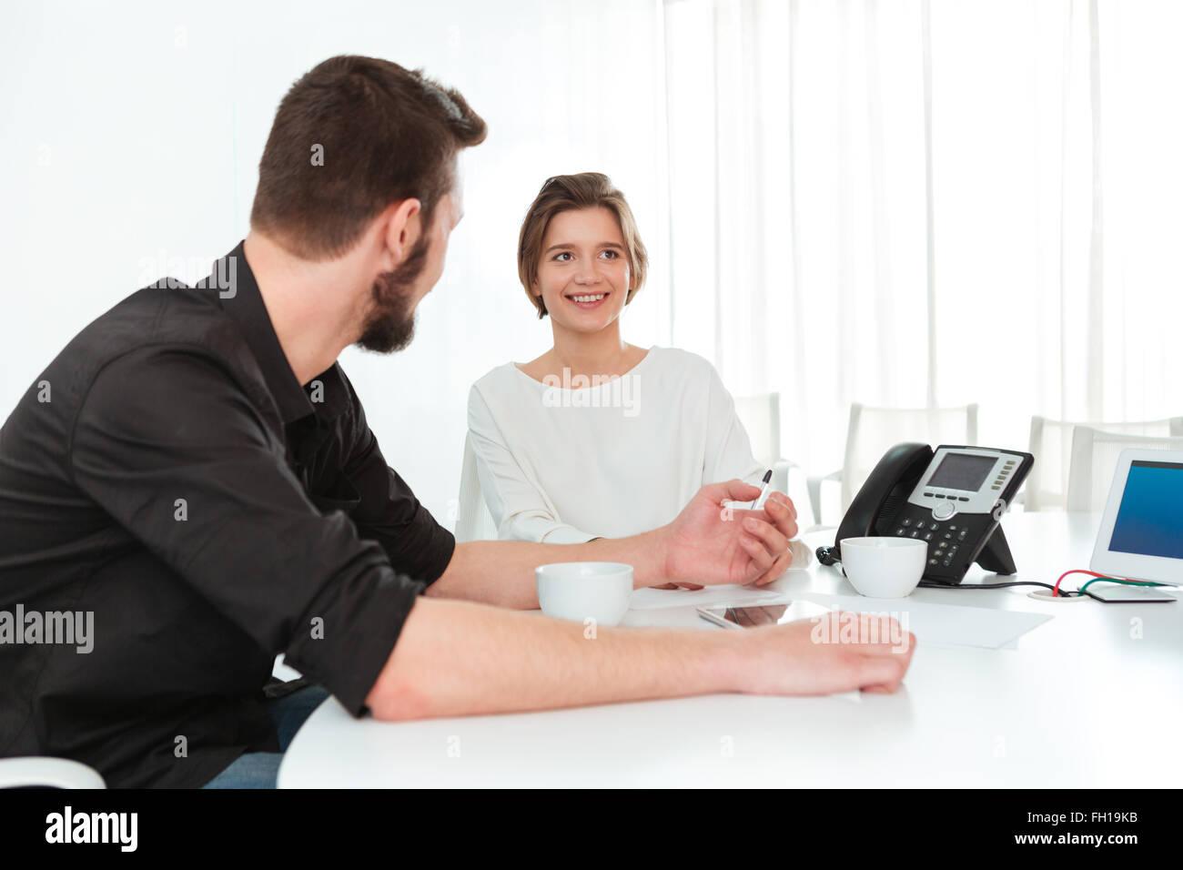 Zwei lächelnde junge Geschäftsleute sitzen und reden auf der Sitzung im Büro Stockbild