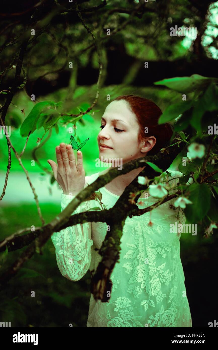 junge Frau im Wald hält einen Schmetterling Stockbild