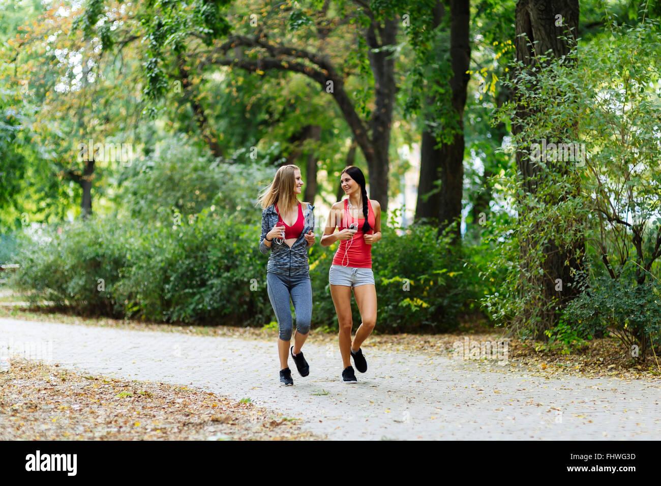 Zwei schöne Frauen im Park Joggen und ihren Körper in Form halten Stockbild