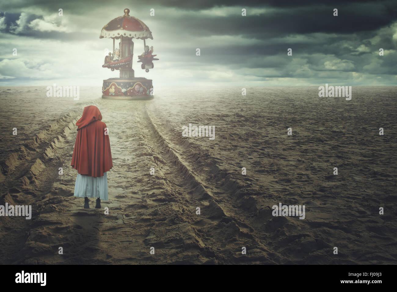 Rot mit Kapuze Frau an einem seltsamen Strand mit Spielzeug-Karussell. Fantasie und surreal Stockbild