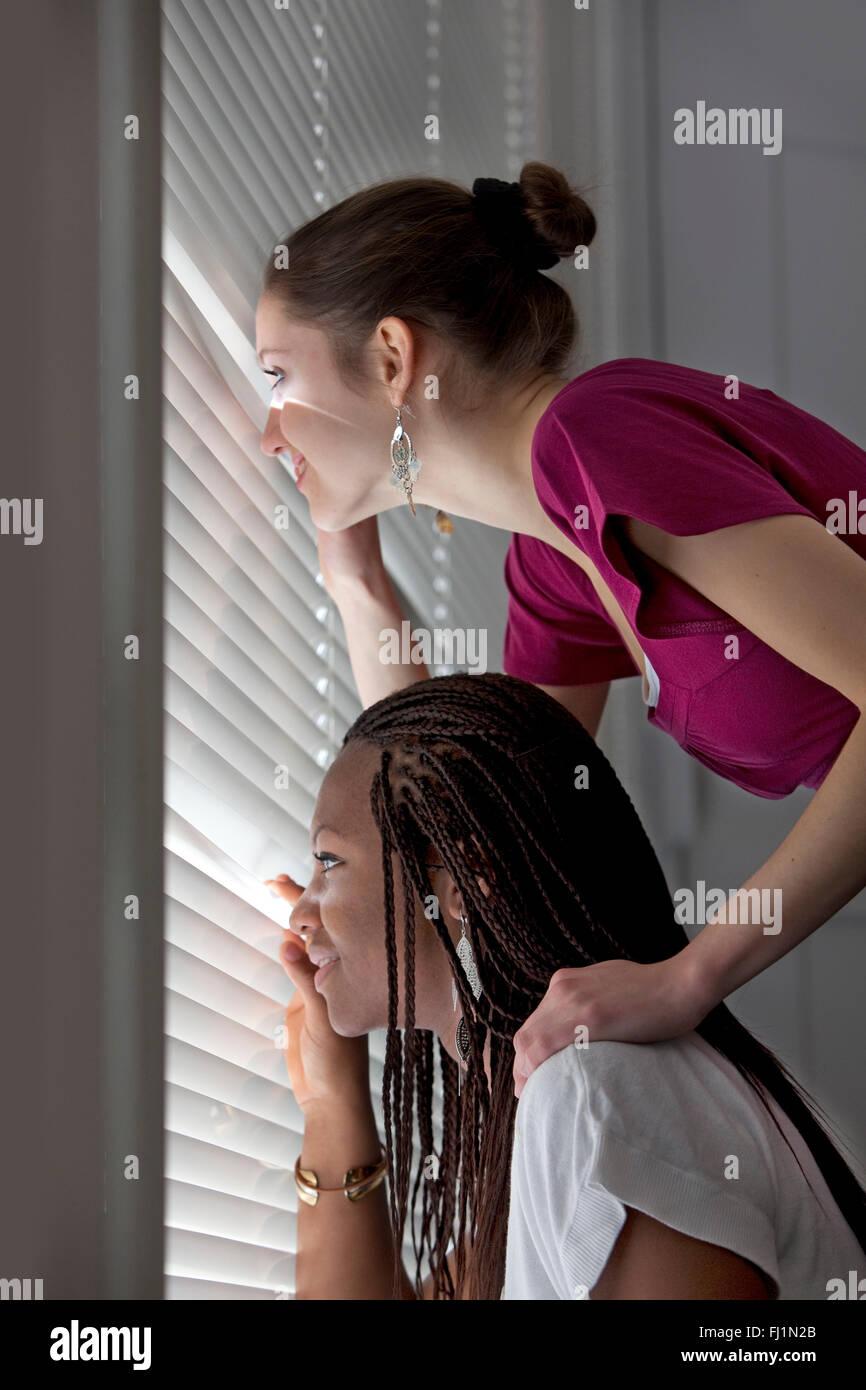 Neugierige Mädchen im Teenageralter sind durch ein Fenster blind suchen. Stockbild