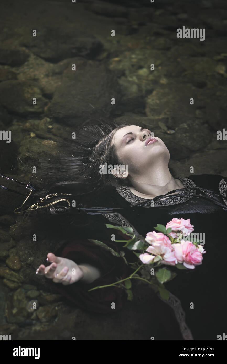Schöne Frau in einem Fluss zu ertränken. Ophelia-Konzept Stockfoto