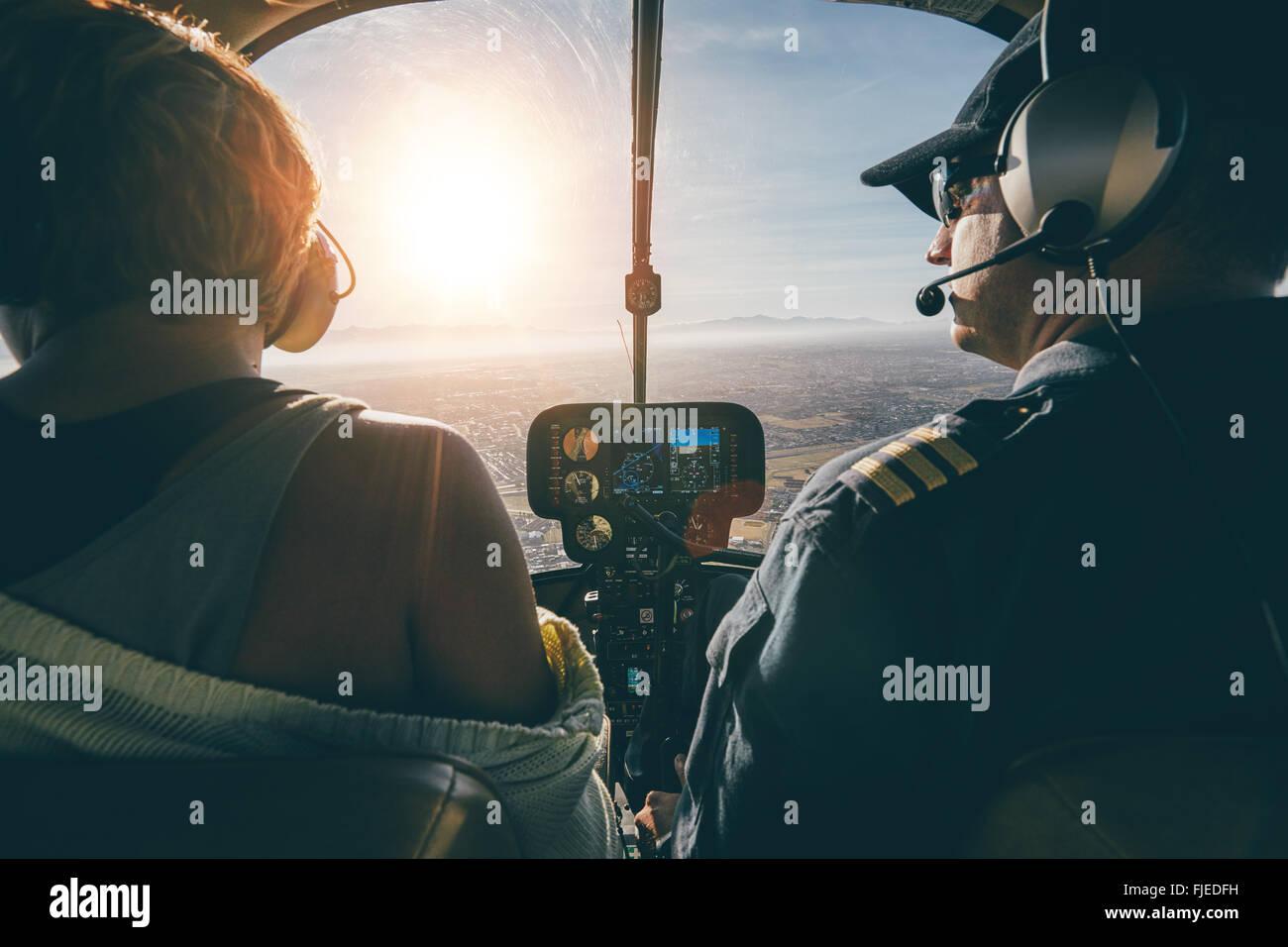 Heckansicht des männlichen und weiblichen Piloten fliegen eines Hubschraubers am sonnigen Tag. Man fliegt einen Stockbild