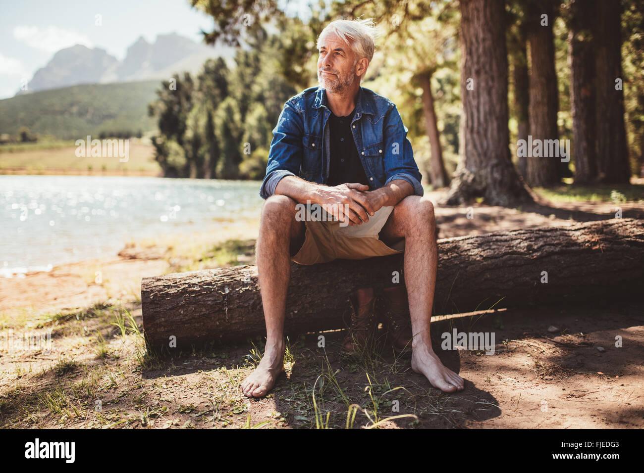 Porträt eines älteren Mannes sitzen auf einem Baumstamm in der Nähe von See und wegsehen. Reifer Stockbild