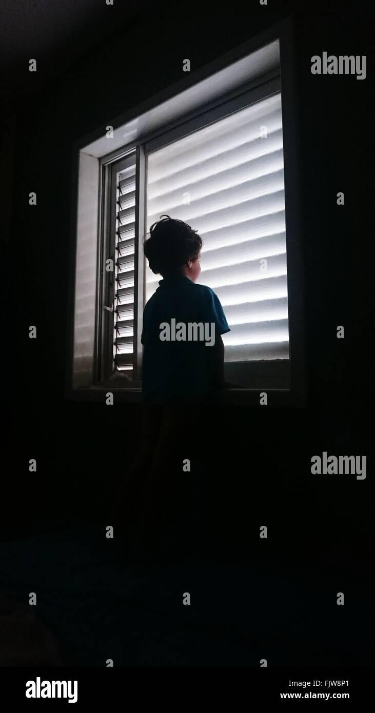 Niedrigen Winkel Ansicht der junge Stand gegen Fenster Stockbild