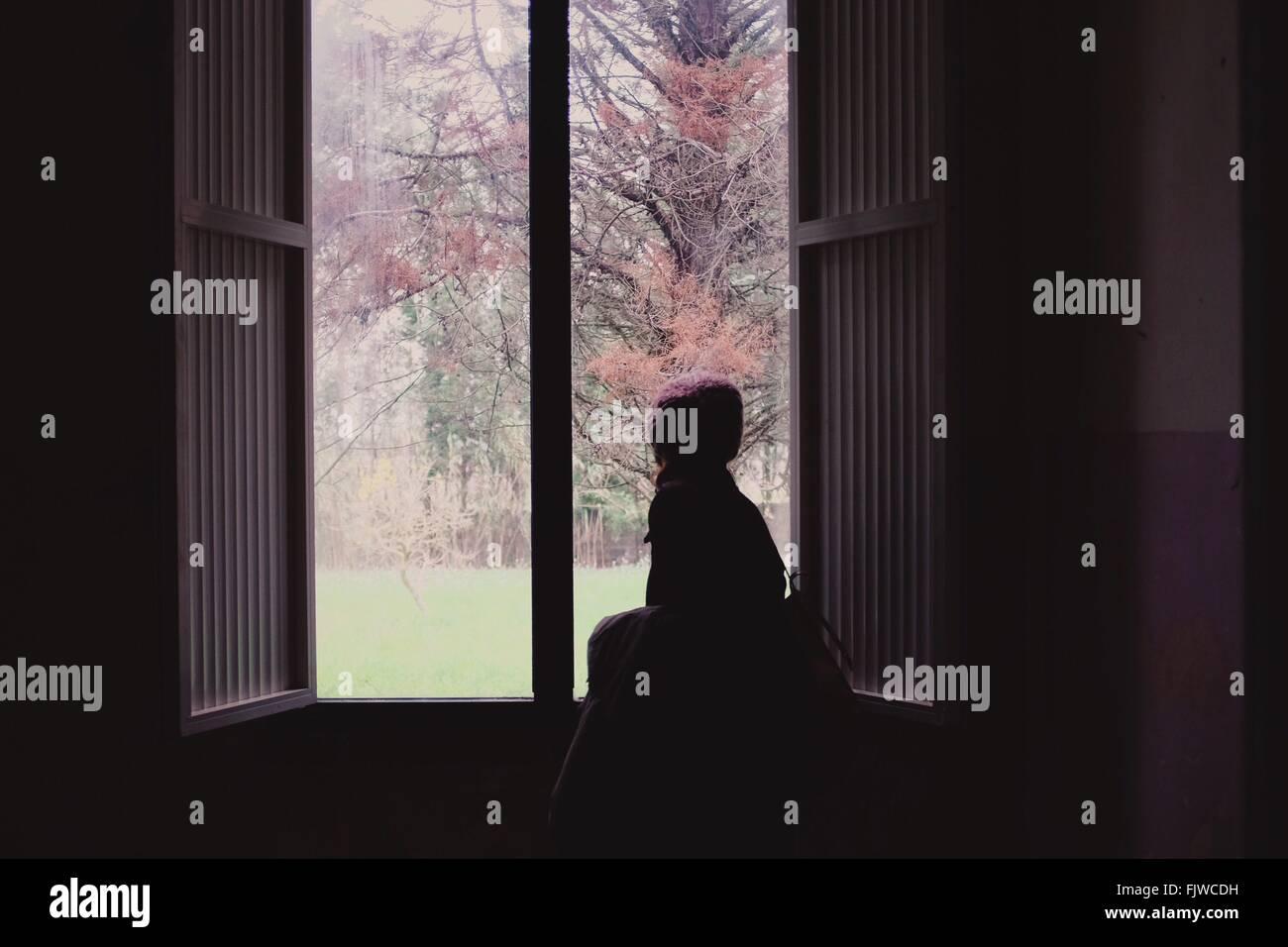Rückansicht eines Mädchens Blick durch Fenster Stockbild