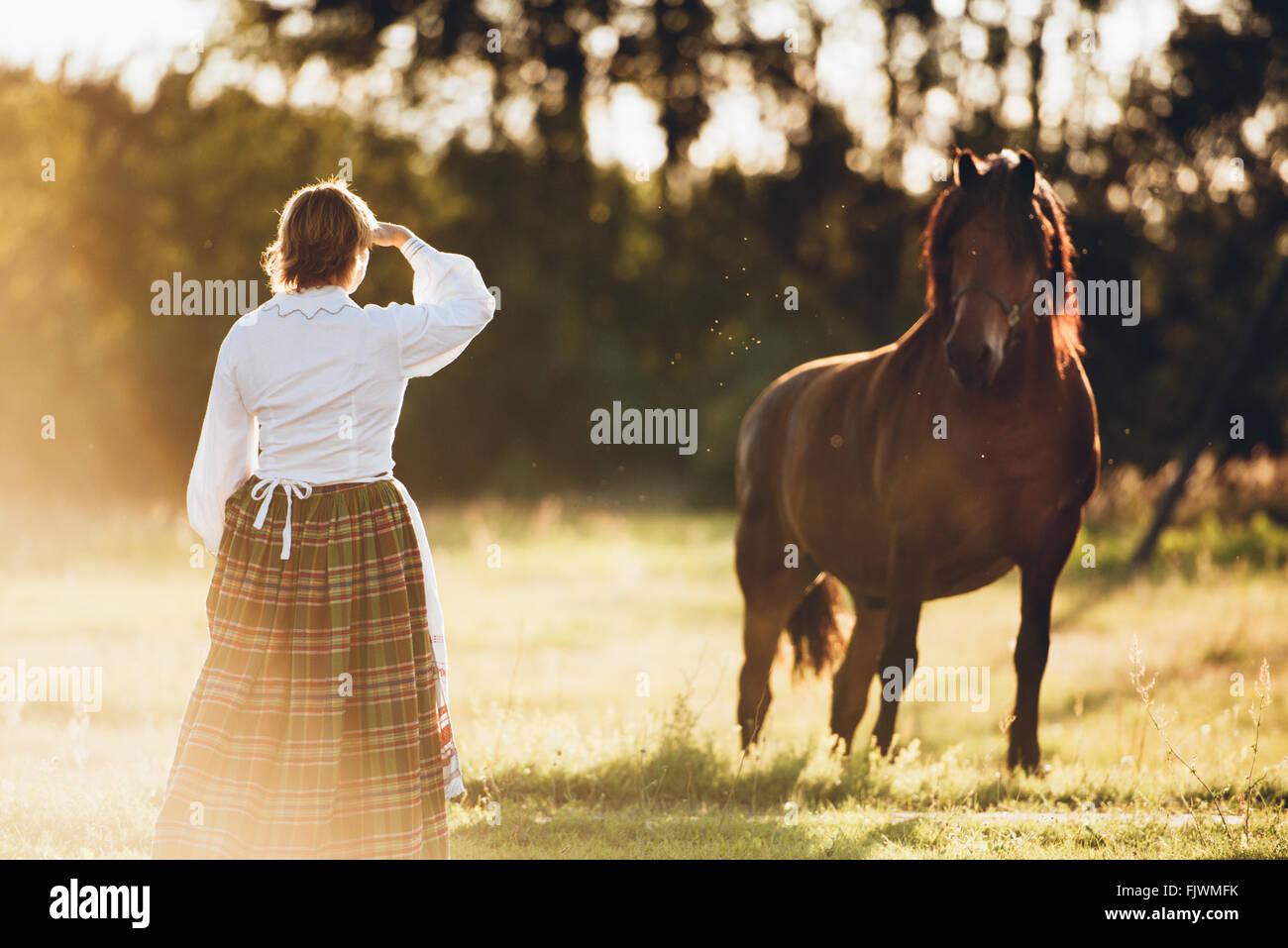 Rückansicht der Frau und Pferd auf Feld stehen Stockbild