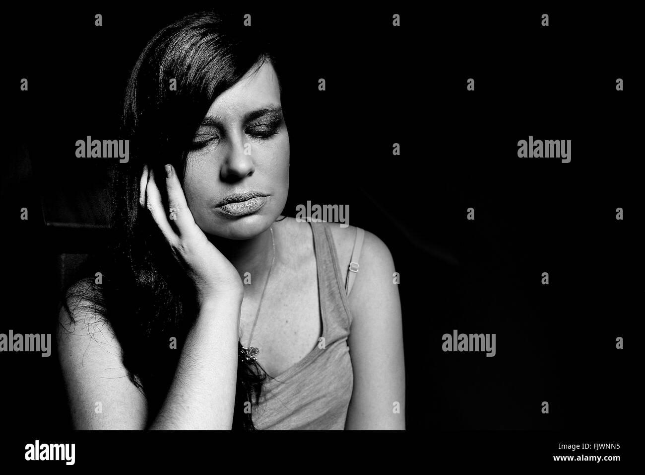 Junge Frau mit Augen geschlossen vor schwarzem Hintergrund Stockbild