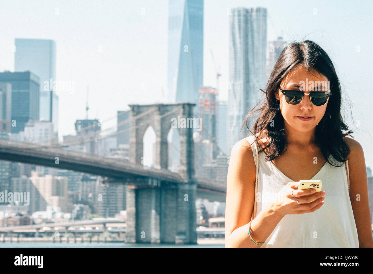 Junge Frau mit Smartphone gegen Brooklyn Bridge Stockfoto