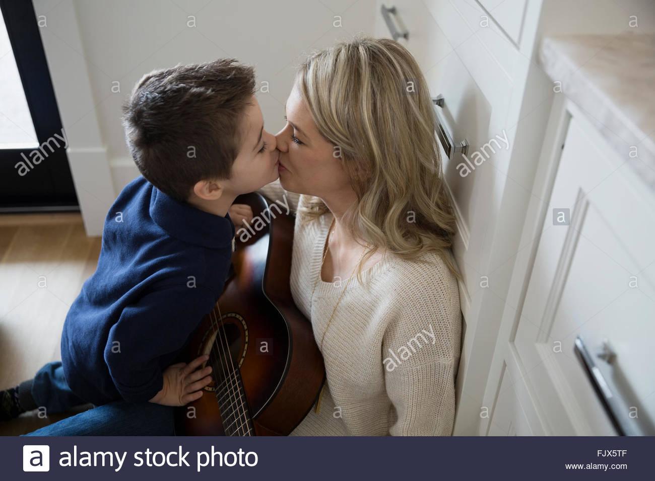 Küssende Mutter Sohn mit Gitarre Stockbild