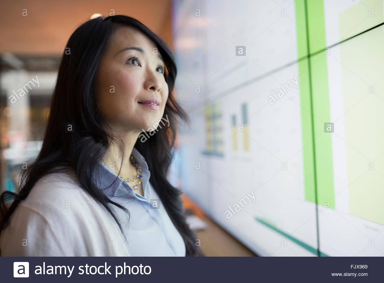 Neugierig blickte zu Projektionsfläche Geschäftsfrau Stockbild