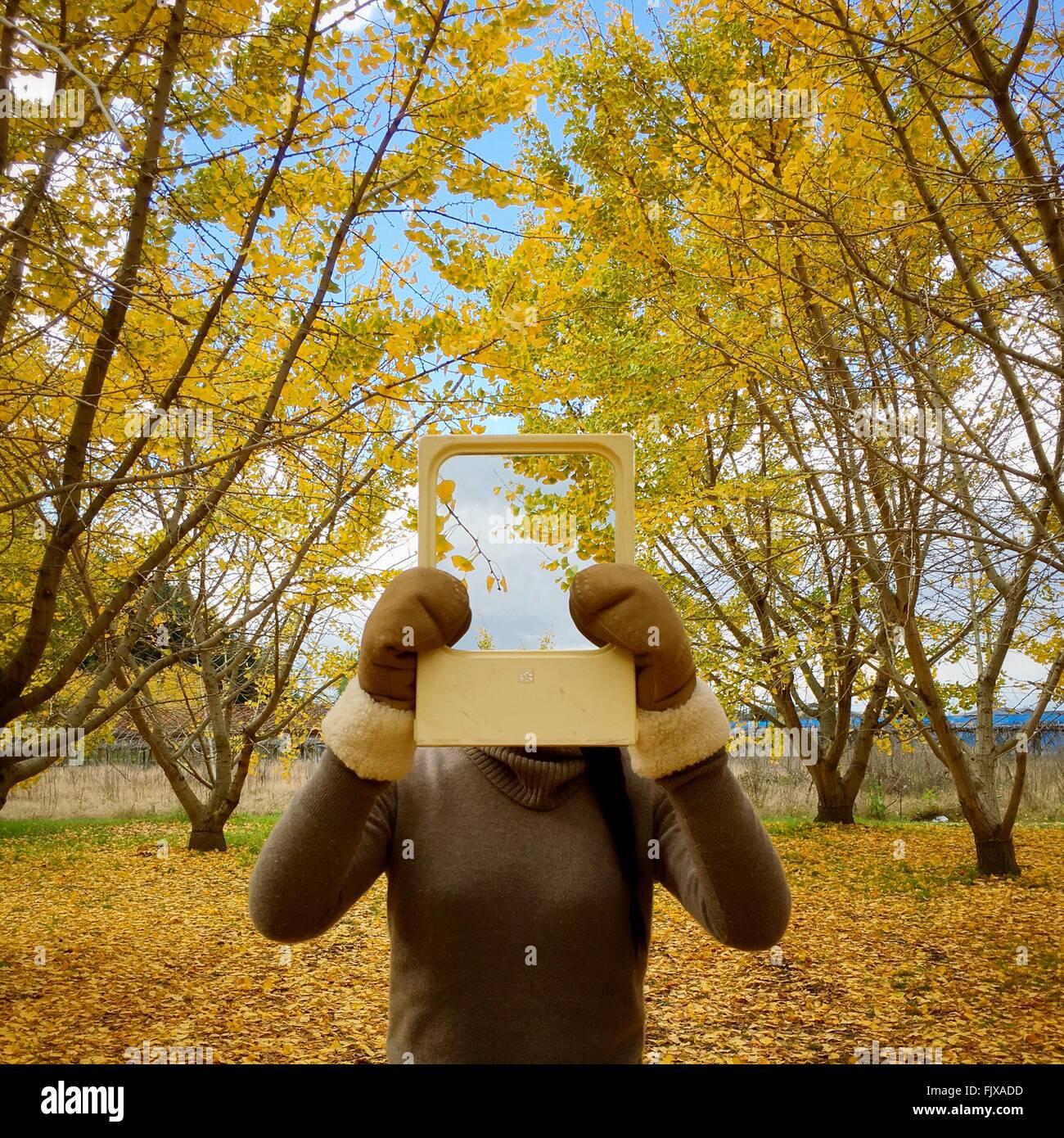 Frau mit Bild von Bäumen vor Gesicht in Nahaufnahme Stockbild