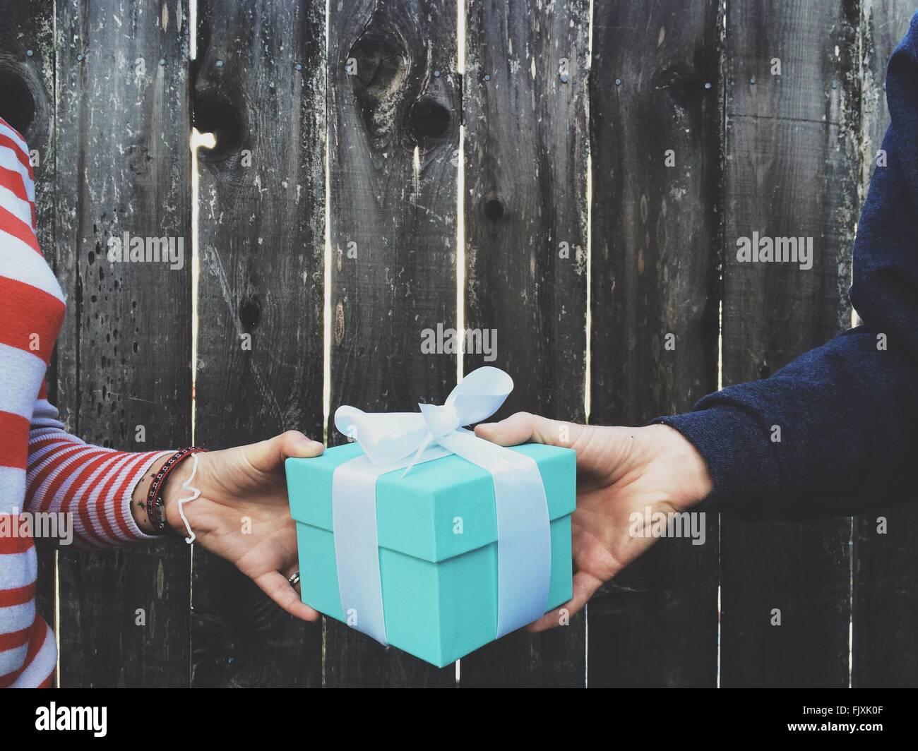 Bild von Händen mit Geschenkbox gegen Holzzaun beschnitten Stockbild