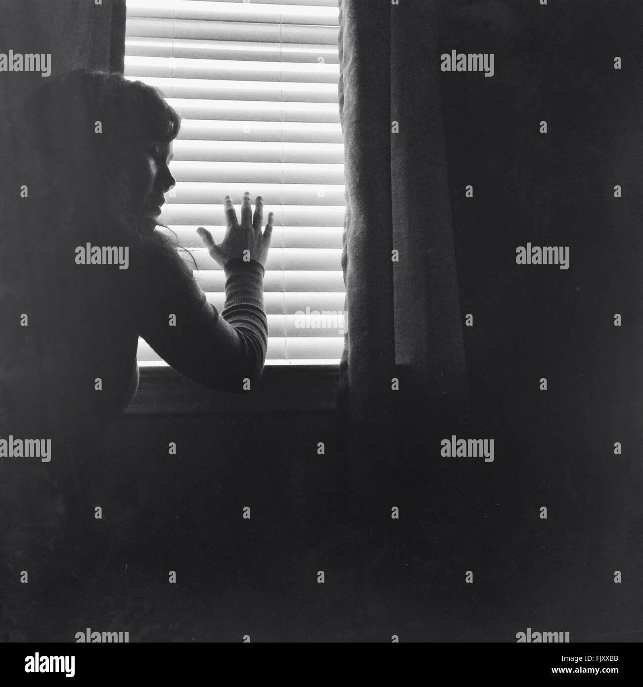 Junge Frau gegen Fenster zu Hause Stockbild
