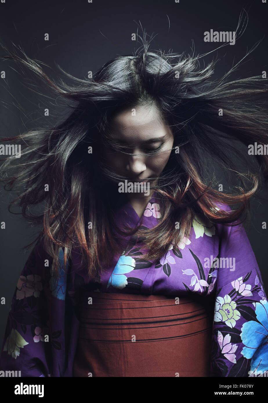 Porträt einer japanischen Frau mit traditionellen Kimono. Dunkle Studioaufnahme Stockbild