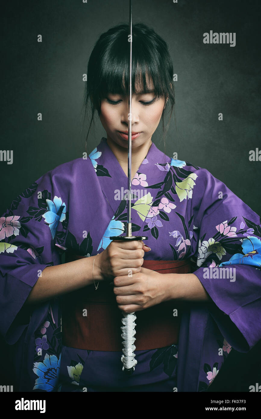 Samurai Frau bereit, mit Katana zu kämpfen. Dunkle Studioaufnahme Stockbild