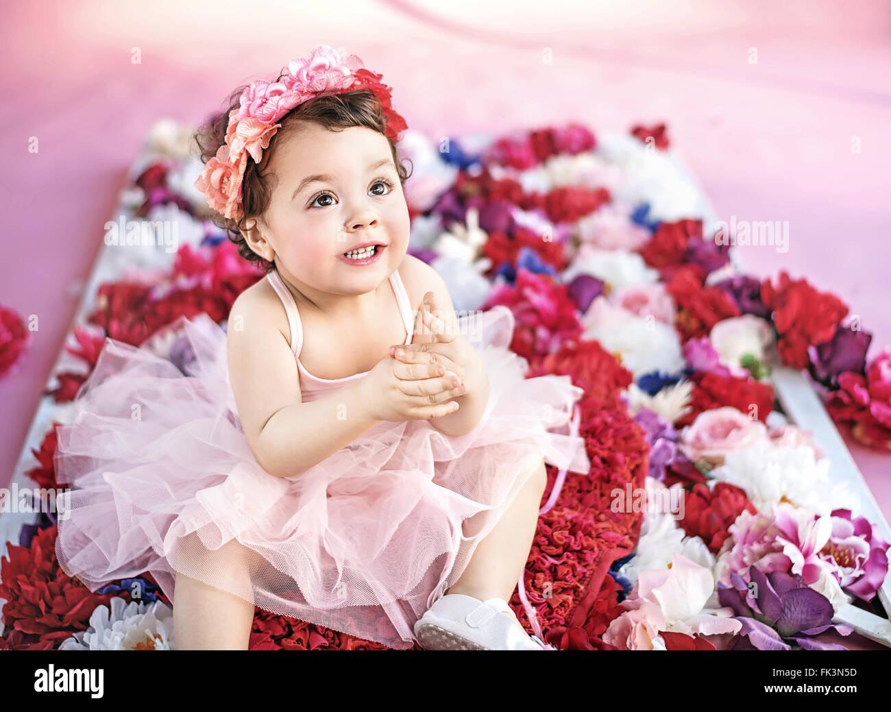 Niedliche Mädchen sitzen auf einem Blumenstrauß Stockbild