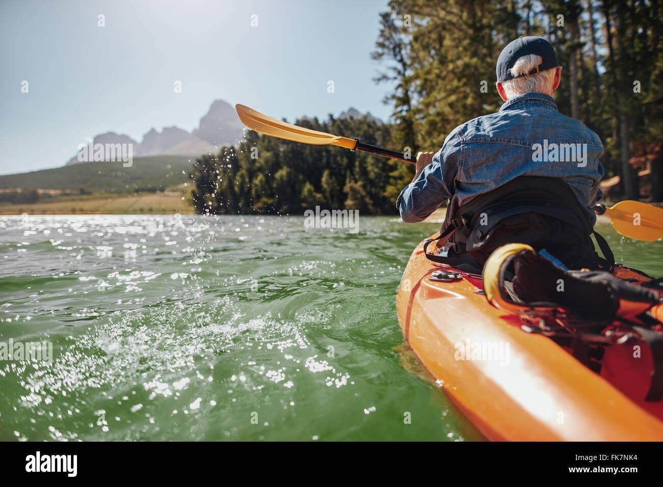 Rear View-Bild eines Mannes in einem See paddeln. Mann eine Kajak paddeln, an Sommertagen. Stockbild