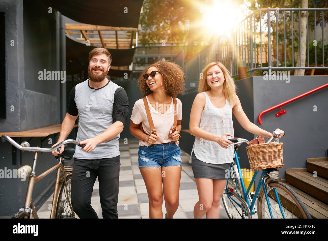 Drei junge Erwachsene gehen gemeinsam Spass haben. Jugendliche mit Fahrrädern zu Fuß im Freien, in der Stockbild