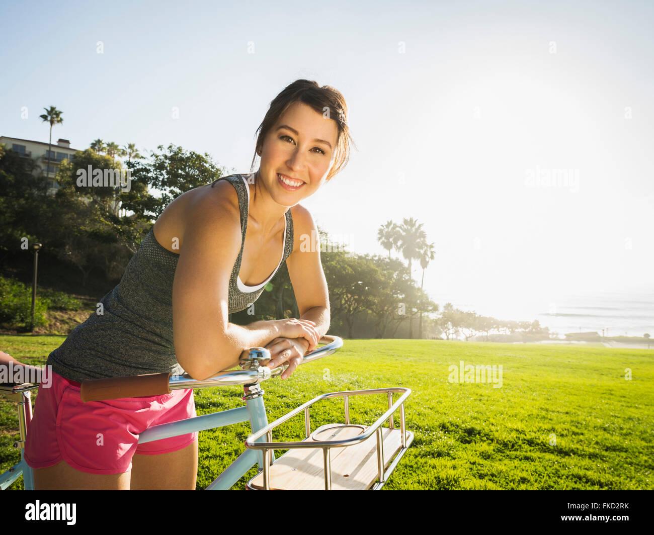 Junge Frau mit dem Fahrrad im park Stockbild