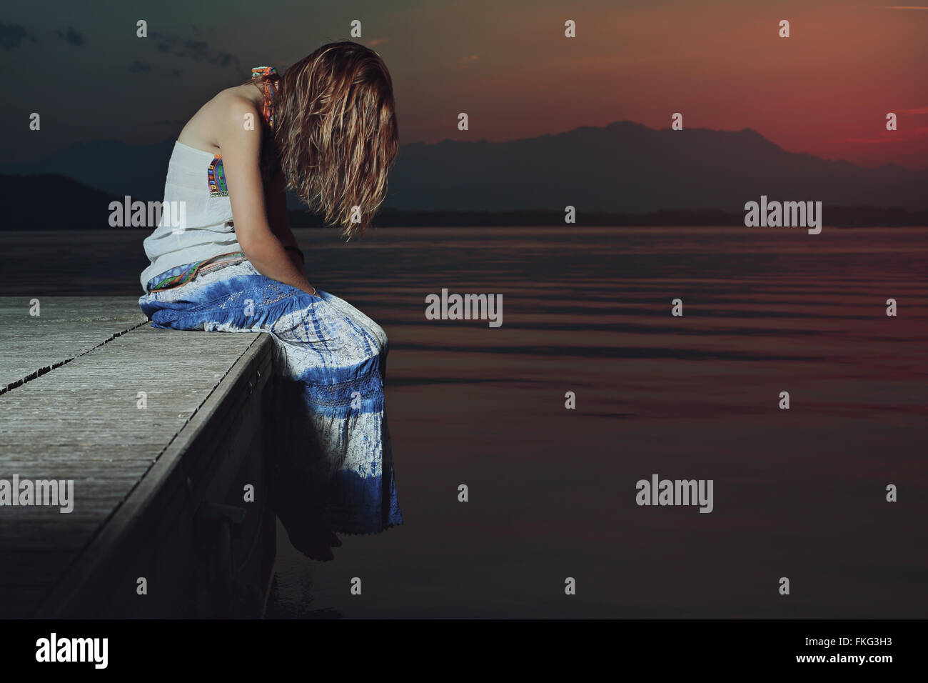 Einsame Frau in traurige Lage über Wasser. Leichte rote Dämmerung Stockbild