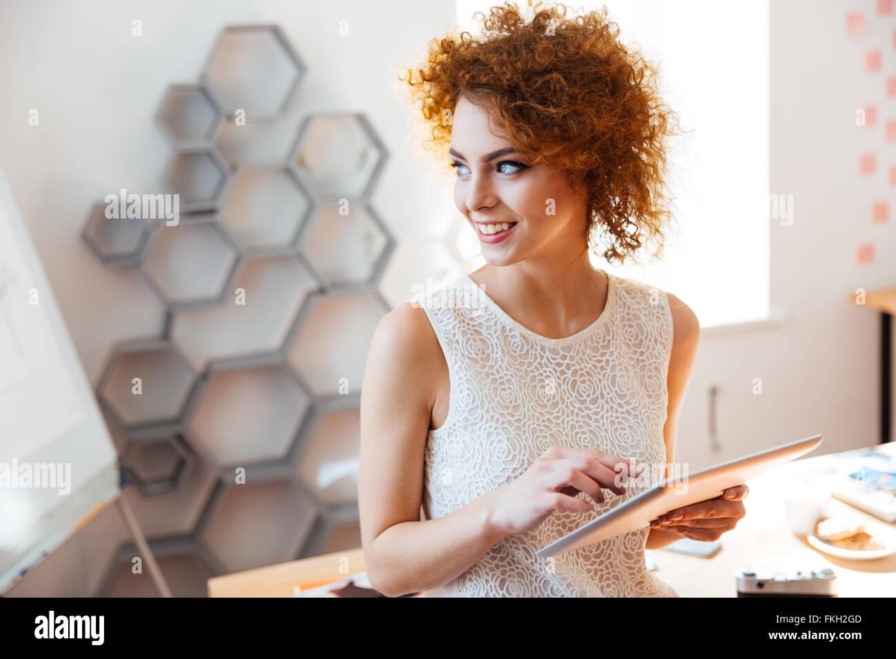 Fröhlich niedliche lockige junge Geschäftsfrau stehend und mit Tablet im Büro Stockbild
