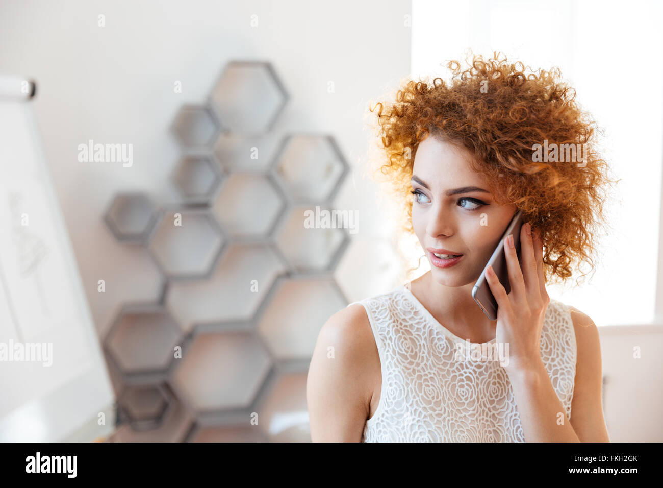 Nachdenkliche schöne junge Geschäftsfrau reden über Handy im Büro Stockbild