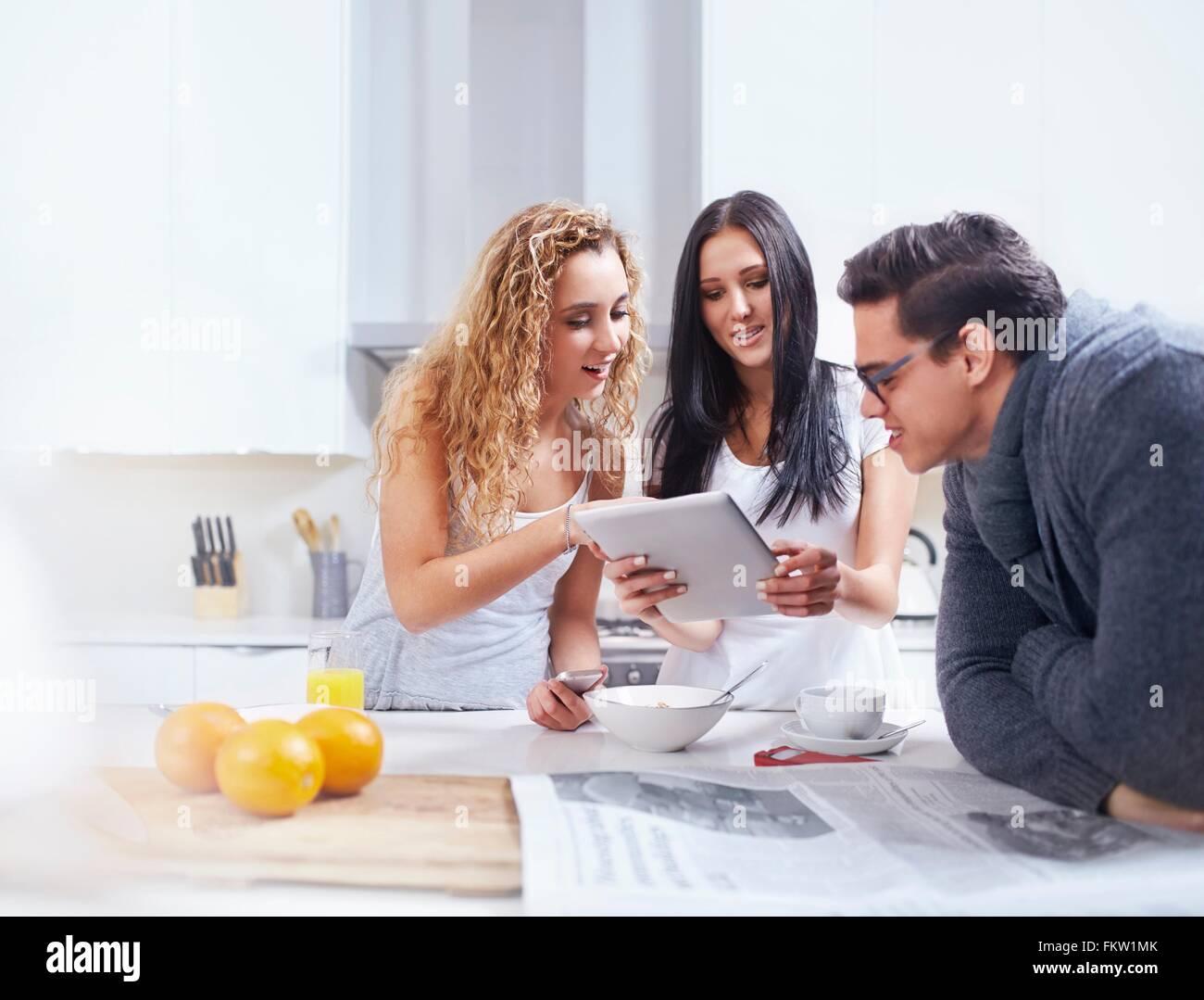 Drei junge Erwachsene, die mit digital-Tablette am Küchentisch Stockbild