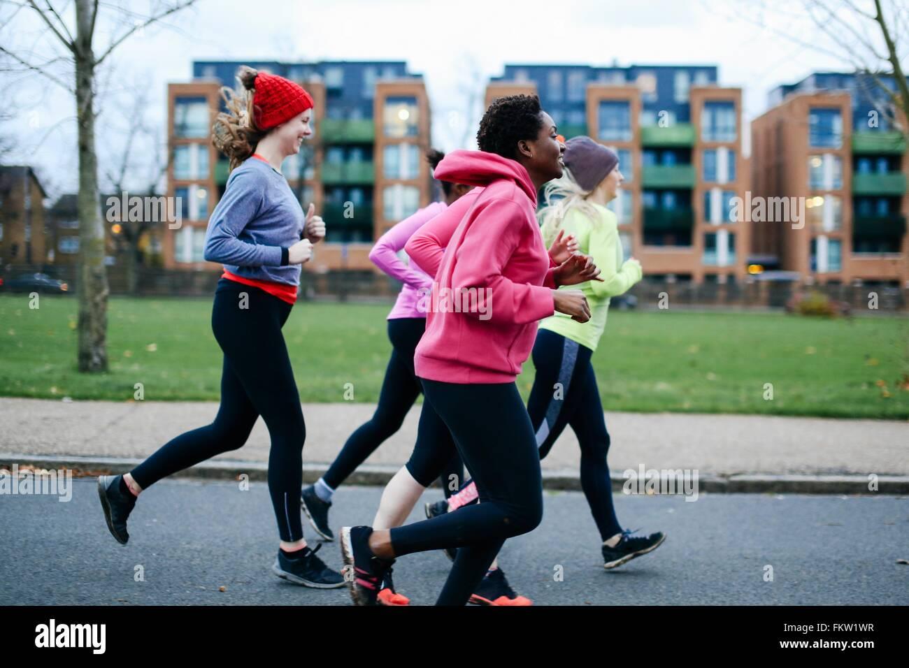 Fünf Läuferinnen, die entlang der Stadt Bürgersteig Stockbild