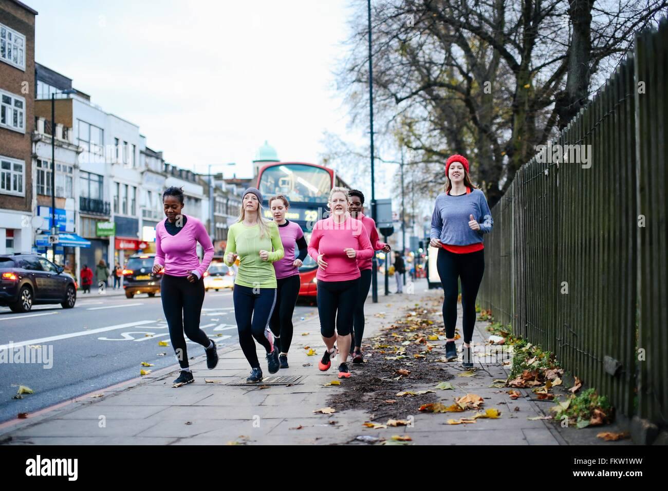 Fünf Läuferinnen laufen auf Stadt Bürgersteig Stockbild