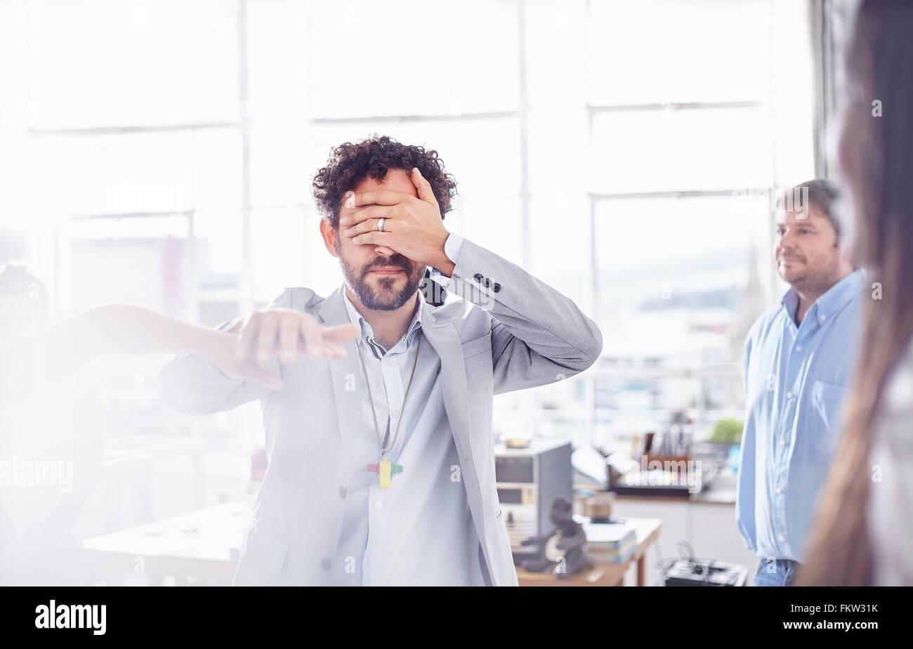 Reifer Mann im Team-building Aufgabe, Hand in Hand für Augen Stockbild