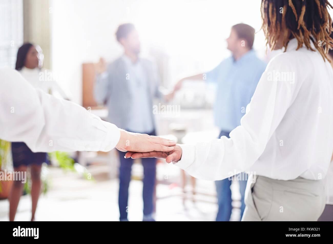Kolleginnen und Kollegen im Team-building Aufgabe stehen im Kreis, die Hand in Hand Stockbild