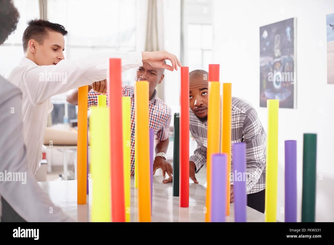 Kolleginnen und Kollegen im Team-building Aufgabe Ausgleich bunte Rohre Stockbild