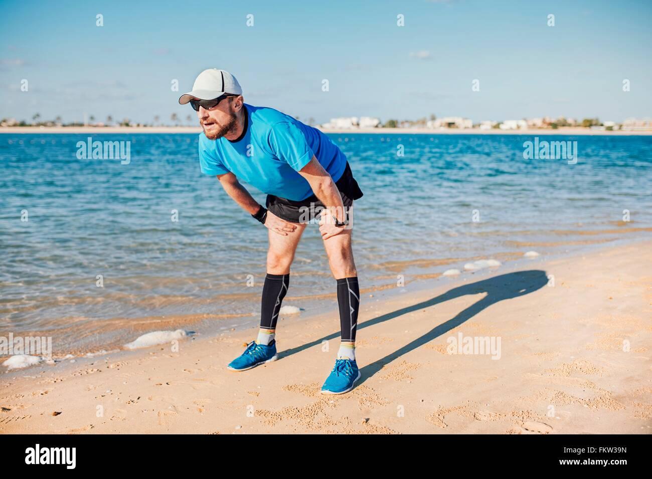 Mitte erwachsenen Mannes an Küste nach vorne biegen wegsehen, Dubai, Vereinigte Arabische Emirate Stockbild